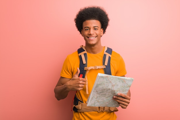 Homem jovem explorador americano africano, segurando um mapa sorrindo e levantando o polegar