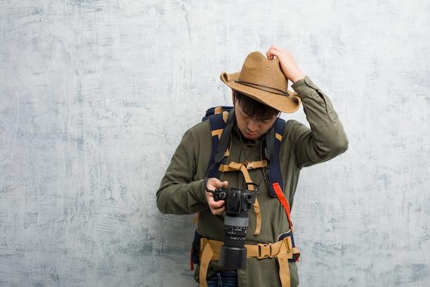 Homem jovem explorador chinês segurando um preocupado e oprimido