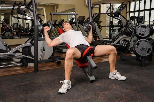 Homem jovem, fazendo, dumbbell incline, imprensa banco, malhação, em, ginásio