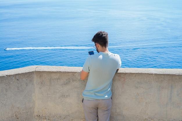 Homem jovem, fazendo exame uma foto, frente, mar