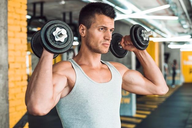 Homem jovem, fazendo, exercício, com, dumbbells, para, fortalecer, seu, ombro