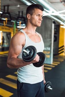 Homem jovem, fazendo, exercício, com, dumbbells