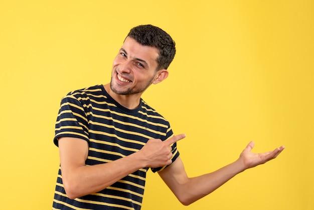 Homem jovem feliz de vista frontal em uma camiseta listrada de preto e branco amarelo fundo isolado