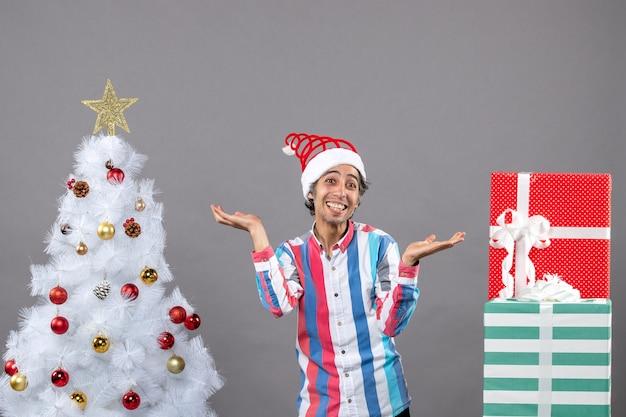Homem jovem feliz em frente a frente com as mãos abertas perto da árvore de natal branca