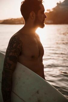 Homem jovem, ficar, com, surfboard, em, mar