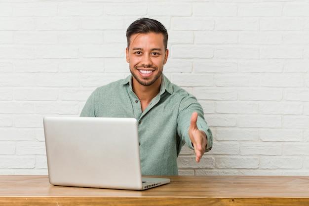 Homem jovem filipino sentado trabalhando com seu laptop, esticando a mão na câmera em gesto de saudação.
