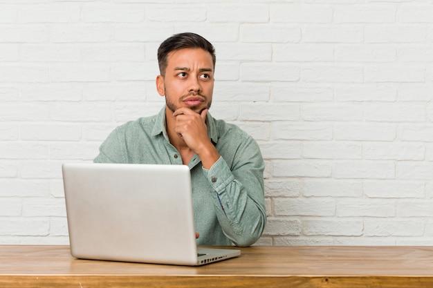Homem jovem filipino sentado trabalhando com seu laptop, olhando de soslaio com expressão duvidosa e cética.