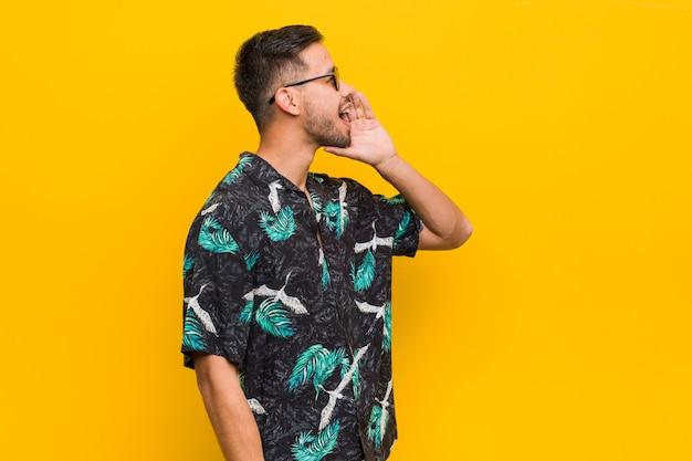 Homem jovem filipino vestindo roupas de verão, gritando e segurando a palma da mão perto da boca aberta.