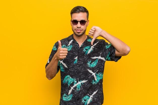 Homem jovem filipino vestindo roupas de verão, mostrando os polegares para cima e os polegares para baixo, difícil escolher o conceito