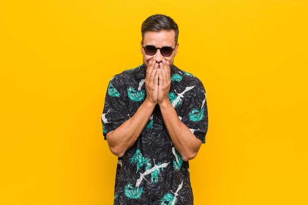 Homem jovem filipino vestindo roupas de verão, rindo de algo, cobrindo a boca com as mãos.