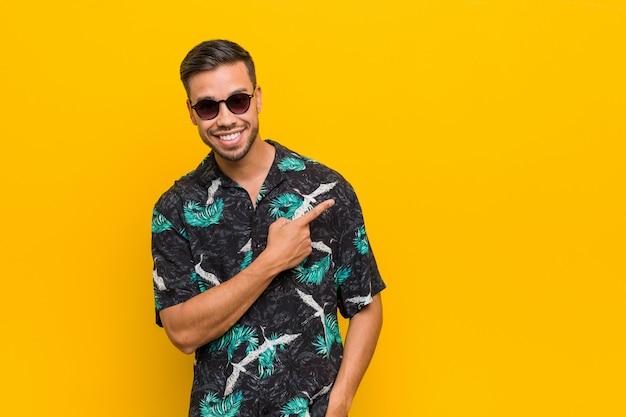 Homem jovem filipino vestindo roupas de verão, sorrindo e apontando de lado, mostrando algo no espaço em branco.