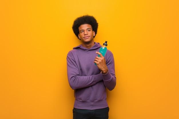 Homem jovem fitness americano africano segurando uma bebida energética sorrindo confiante e cruzando os braços, olhando para cima