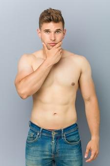Homem jovem fitness caucasiano sem camisa tocando seu queixo.