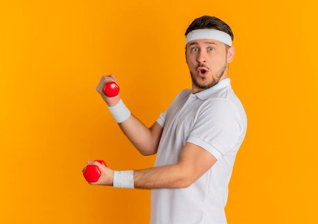 Homem jovem fitness com camisa branca e faixa na cabeça, malhando com halteres, olhando para a frente, sorrindo em pé sobre a parede laranja