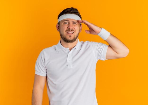 Homem jovem fitness com camisa branca e fita na cabeça, olhando para a frente, confuso com a mão na cabeça em pé sobre a parede laranja