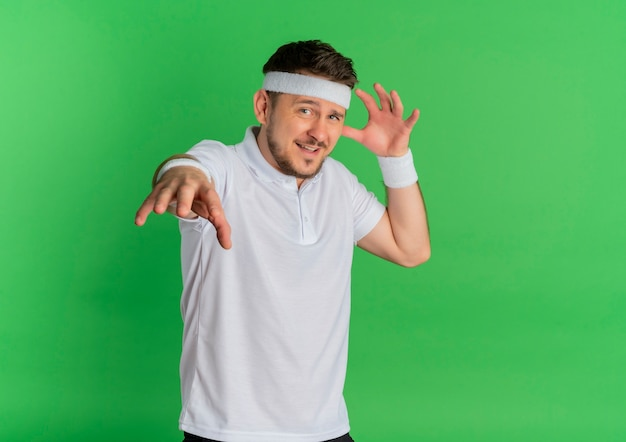 Homem jovem fitness com camisa branca e fita na cabeça, olhando para a frente, feliz e positivo, de mãos dadas em pé sobre a parede verde