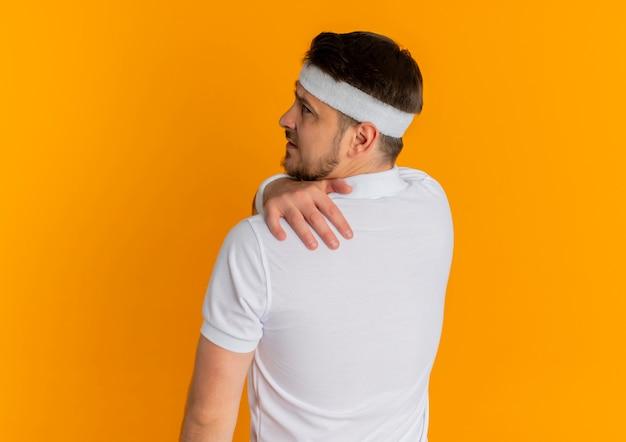 Homem jovem fitness com camisa branca e fita para a cabeça, em pé com as costas tocando seu ombro, sentindo dor na parede laranja