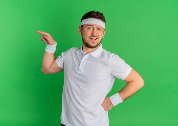 Homem jovem fitness com camisa branca e fita para a cabeça, olhando para a frente, apontando com o dedo para o lado em pé sobre a parede verde