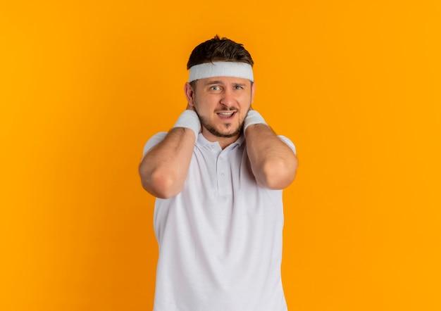 Homem jovem fitness com camisa branca e fita para a cabeça, olhando para a frente, sentindo desconforto em pé sobre a parede laranja