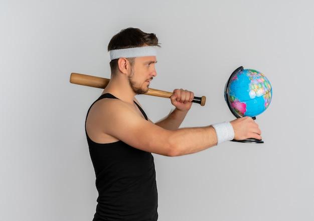 Homem jovem fitness com fita para a cabeça segurando um taco de beisebol e um globo olhando para ele com uma cara séria em pé sobre um fundo branco