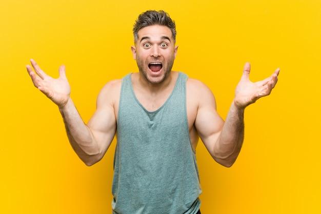 Homem jovem fitness comemorando uma vitória ou sucesso, ele está surpreso e chocado