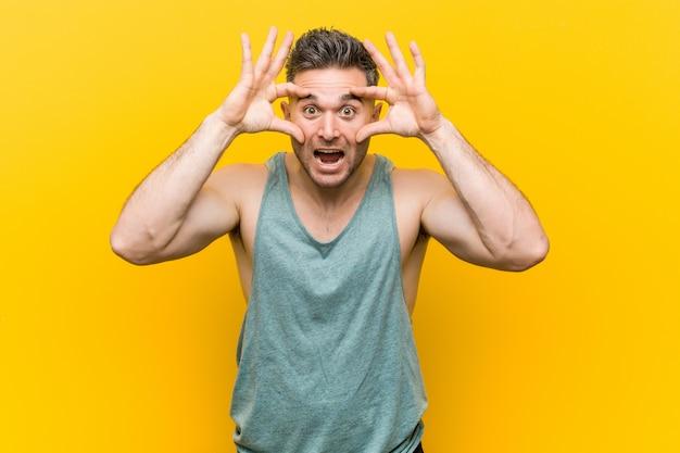 Homem jovem fitness contra um amarelo, mantendo os olhos abertos para encontrar uma oportunidade de sucesso.