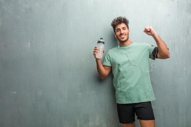 Homem jovem fitness contra uma parede de grunge muito feliz e animado, levantando os braços