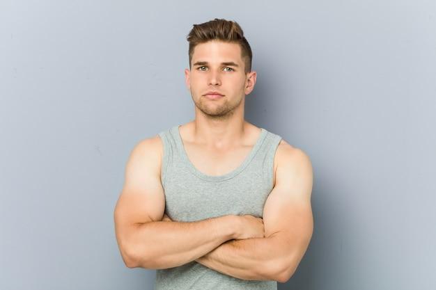 Homem jovem fitness contra uma parede