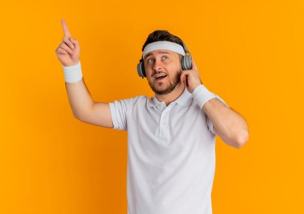 Homem jovem fitness em uma camisa branca com bandana e fones de ouvido, parecendo surpreso e feliz, mostrando o dedo indicador tendo uma ótima ideia em pé sobre a parede laranja