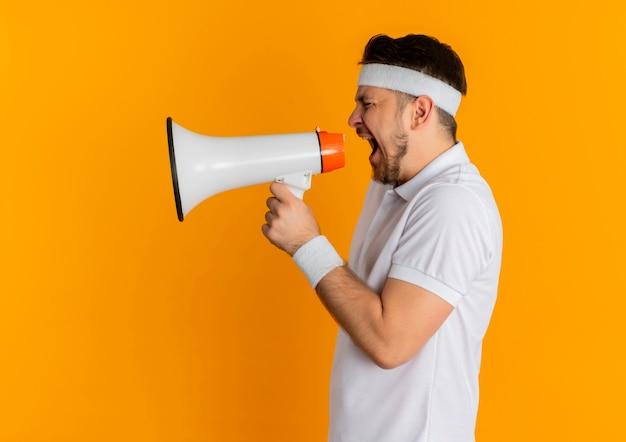 Homem jovem fitness em uma camisa branca com bandana gritando para o megafone e uma expressão agressiva em pé sobre a parede laranja