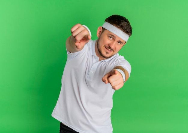 Homem jovem fitness em uma camisa branca com bandana olhando para a frente apontando com o dedo indicador para você com um sorriso no rosto em pé sobre a parede verde