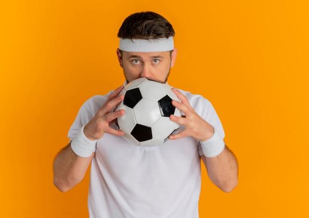 Homem jovem fitness em uma camisa branca com tiara segurando uma bola de futebol, escondendo o rosto atrás dela em pé sobre fundo laranja