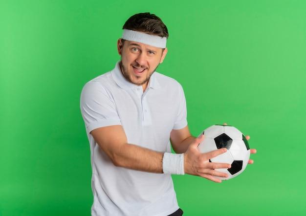 Homem jovem fitness em uma camisa branca com tiara segurando uma bola de futebol, olhando para a câmera, sorrindo alegremente em pé sobre um fundo verde