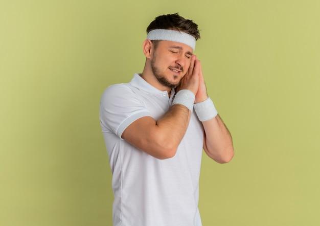 Homem jovem fitness em uma camisa branca com uma faixa na cabeça segurando as palmas das mãos juntas, inclinando a cabeça sobre as palmas com os olhos fechados, quer dormir em pé sobre um fundo verde-oliva