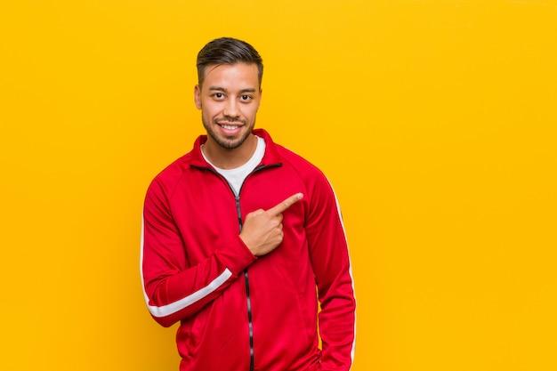 Homem jovem fitness filipino sorrindo e apontando de lado, mostrando algo no espaço em branco.