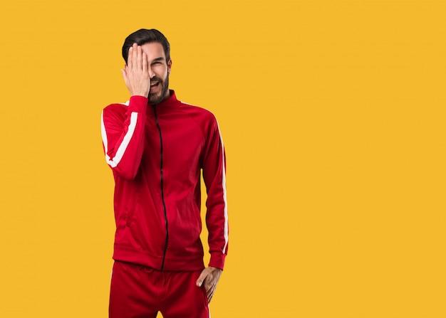 Homem jovem fitness gritando feliz e cobrindo o rosto com a mão