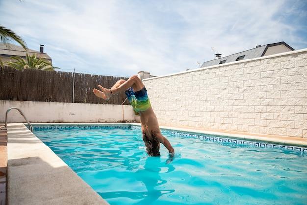 Homem jovem fitness pulando na água na piscina um dia de férias de verão