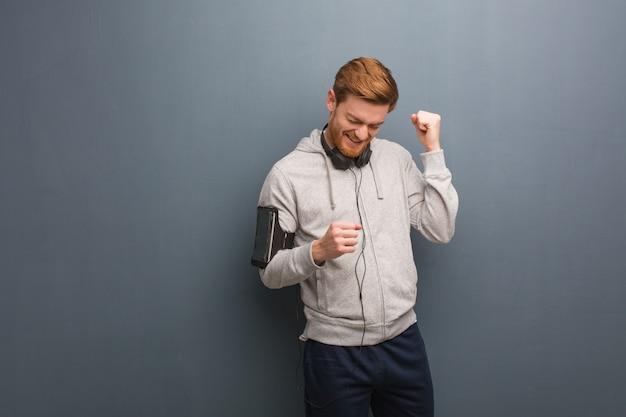 Homem jovem fitness ruiva dançando e se divertindo