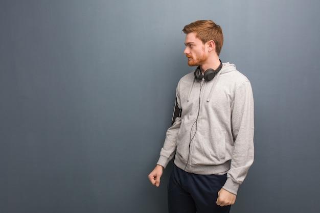 Homem jovem fitness ruiva do lado olhando para frente