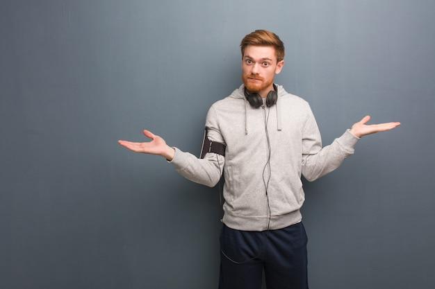 Homem jovem fitness ruiva duvidando e encolher os ombros