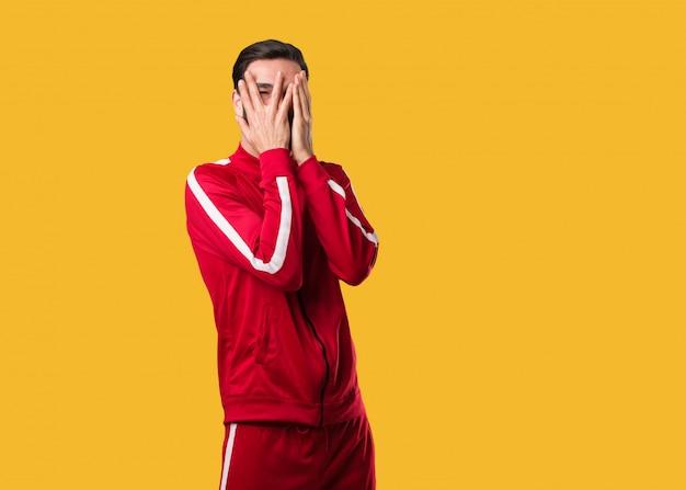 Homem jovem fitness sente-se preocupado e assustado