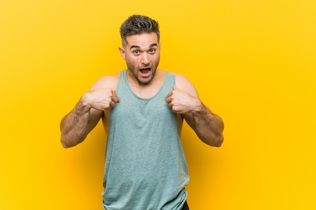 Homem jovem fitness surpreendeu apontando com o dedo, sorrindo amplamente
