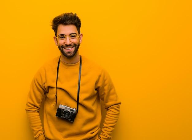 Homem jovem fotógrafo alegre com um grande sorriso