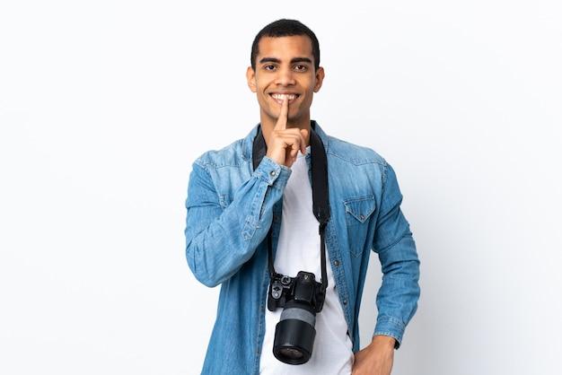 Homem jovem fotógrafo americano africano sobre parede branca isolada, fazendo o gesto de silêncio