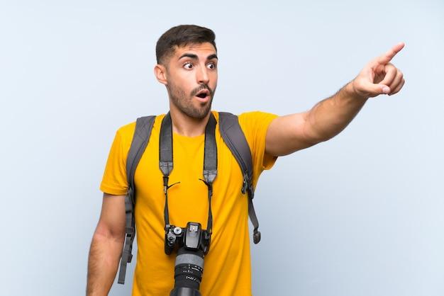 Homem jovem fotógrafo apontando para fora