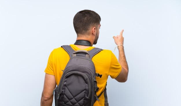 Homem jovem fotógrafo apontando para trás com o dedo indicador