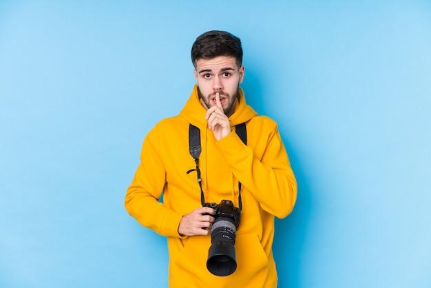Homem jovem fotógrafo caucasiano isolado mantendo um segredo ou pedindo silêncio.
