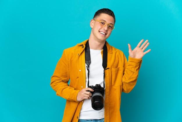Homem jovem fotógrafo, caucasiano, isolado no azul, saudando com a mão e expressão feliz.