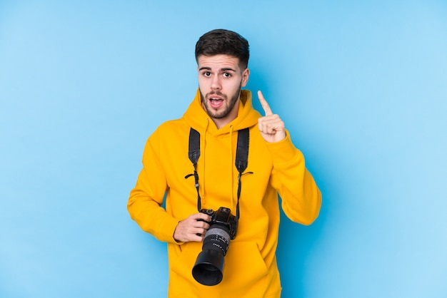 Homem jovem fotógrafo caucasiano isolado tendo uma ideia, o conceito de inspiração.