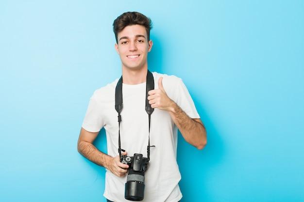 Homem jovem fotógrafo caucasiano segurando sorrindo e levantando o polegar